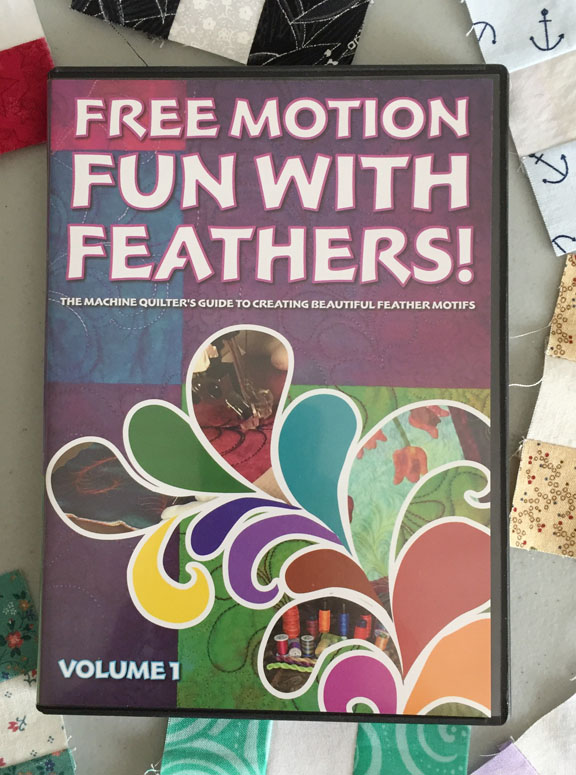 Image of the cover of a DVD called Free Motion Fun with Feathers! The Machine Quilter's Guide to Creating Beautiful Feather Motifs, Volume 1. The DVD rests on a background of small nine-patch quilt blocks.