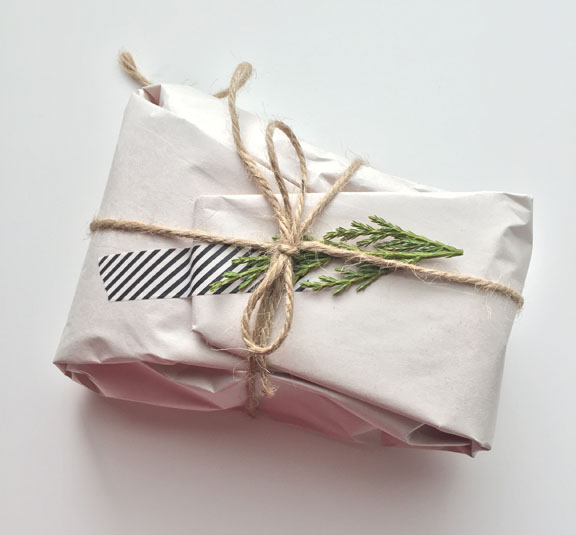 A package wrapped in white shipping paper and secured with black and white stripped washi tape. Tied with a string and adorned with a sprig of greenery
