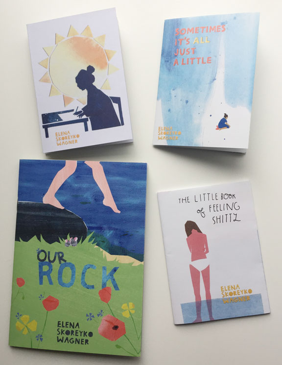 "A set of four zines by Elena Skoreyko Wagner, Sometimes It's All Just a Little, A woman in front of a sun, a book called ""Our Rock"", and The Little Book of Feeling Shitty"
