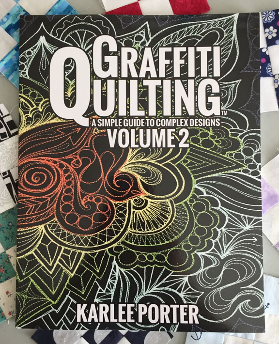 Image of the cover of Karlee Porter's book, titled Graffiti Quilting: A Simple Guide to Complex Designs, Volume 2. The book rests on a background of small nine-patch quilt blocks.
