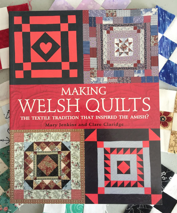 Image of the cover of Mary Jenkins and Clare Claridge's book, titled Making Welsh Quilts: The Textile Tradition that Inspired the Amish? The book rests on a background of small nine-patch quilt blocks.