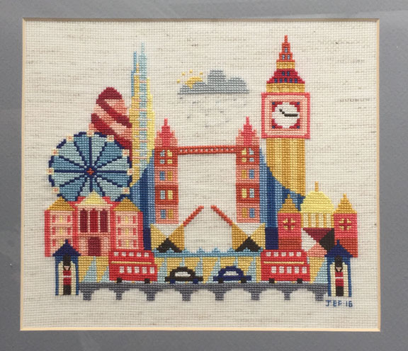 A modern cross stitch depicting iconic buildings from London, England including the London Eye, the London Bridge, the Shard, the Gherkin, Big Ben, St. Paul's Cathedral, Buckingham Palace, london taxis, and red double decker buses.