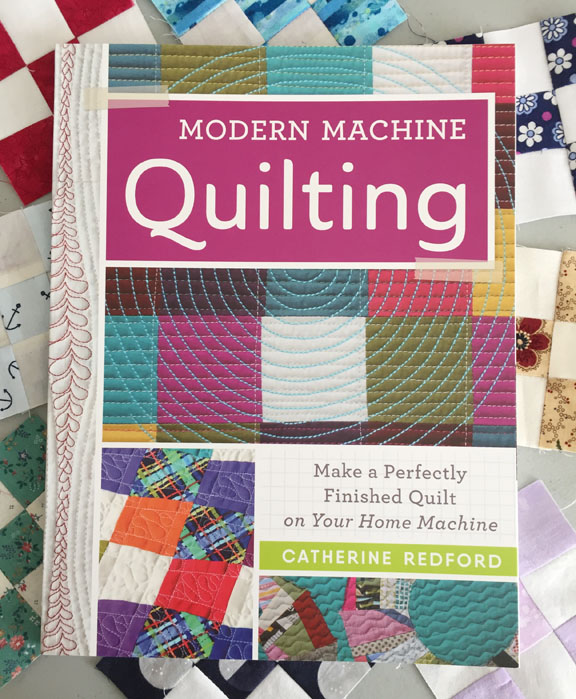 Image of the cover of Catherine Redford's book, titled Modern Machine Quilting: Make a Perfectly Finished Quilt on Your Home Machine. The book rests on a background of small nine-patch quilt blocks.