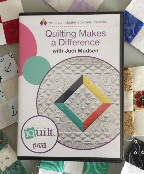 Image of the cover of a DVD called Quilting Makes a Difference with Judi Madsen. The DVD rests on a background of small nine-patch quilt blocks.